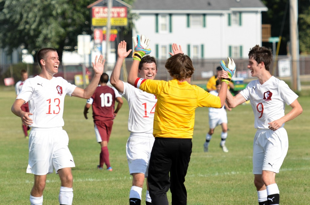 Steig Theden is congratulated by teammates after scoring on a goal kick.