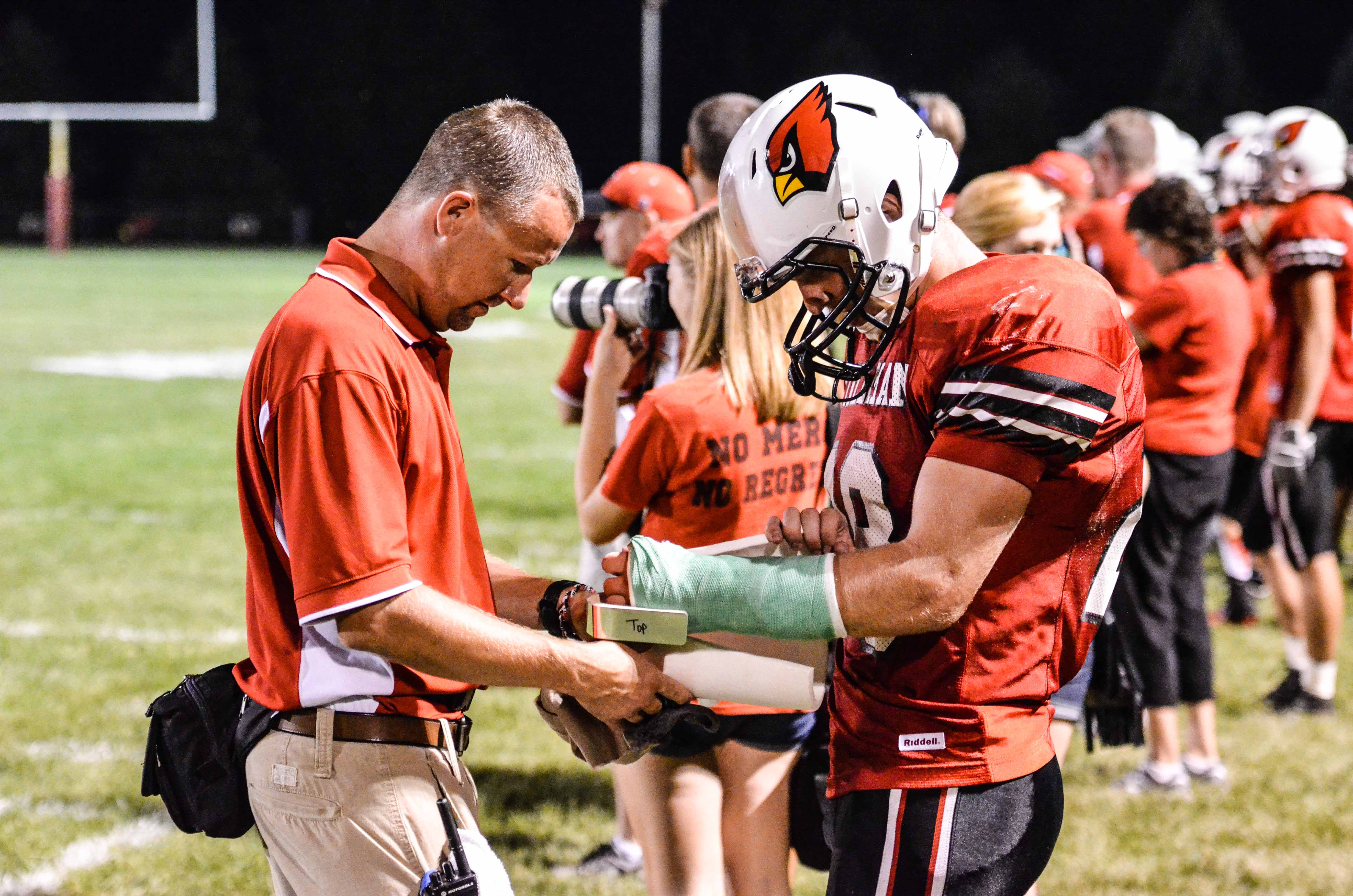 Trainer Aaron removes padding from the most well wrapped cast in high school football